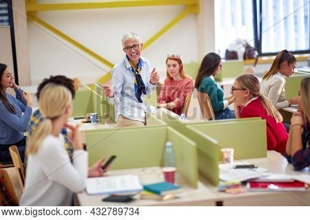 Female professor enjoying in a discussion with students in the classroom