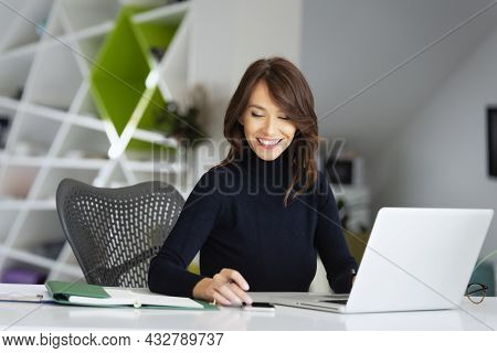 Businesswoman Wearing Turtleneck Sweater And Writing Something While Using Laptop At The Office