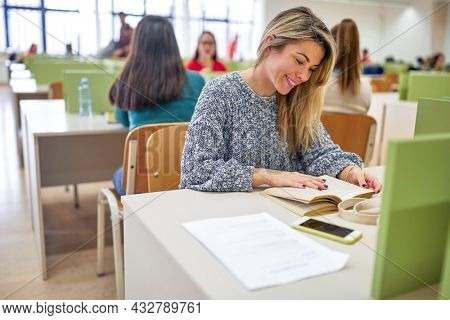 A female student enjoying reading a textbook at the lecture in the university classroom. Smart young people study at the college. Education, college, university, learning and people concept