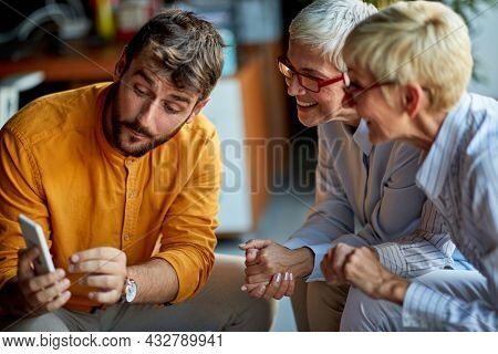 A young male colleague is showing smartphone content to two older business women of similar appearance during a break in a friendly atmosphere at workplace. Business, office, job