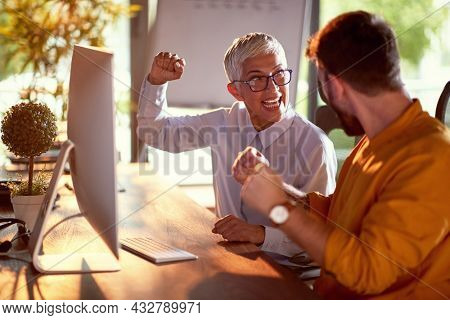A young businessman and elderly female colleague are yelling and celebrating a done job the are working together on at the desk in a working atmosphere at workplace. Business, office, job