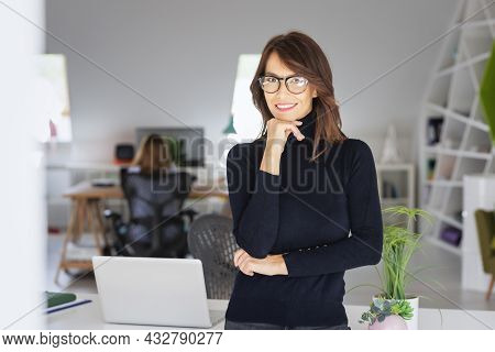 Portrait Of Attractive Middle Aged Businesswoman Wearing Eyeglasses And Turtleneck Sweater While Sta