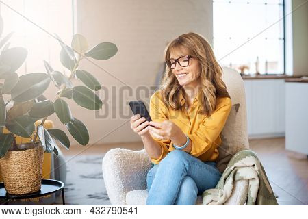 Portrait Shot Of Happy Middle Aged Woman Using Mobile Phone And Text Messaging While Relaxing In The