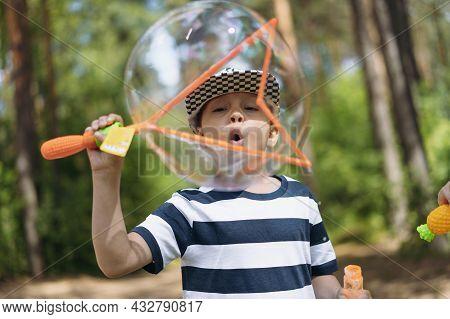 Cute Caucasian Boy Blowing Huge Soap Bubble