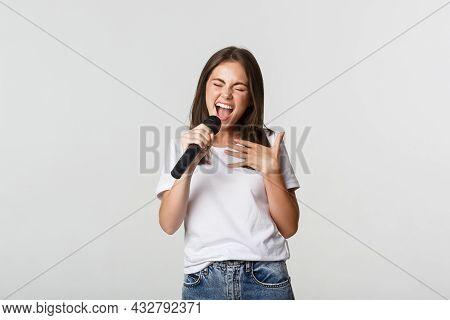 Carefree Beautiful Girl Singing Karaoke, Holding Microphone, Standing White Background