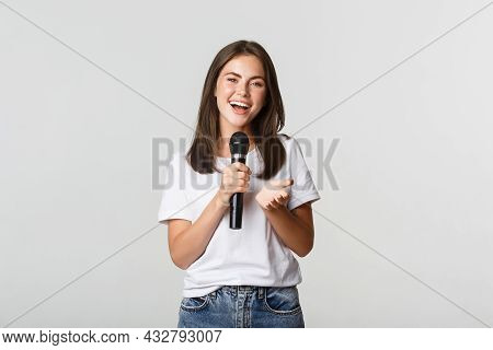 Beautiful Young Woman Singing Song In Microphone At Karaoke, Standing White Background