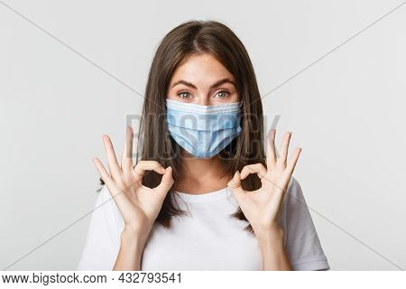 Covid-19, Health And Social Distancing Concept. Close-up Of Pretty Satisfied Girl In Medical Mask Sh
