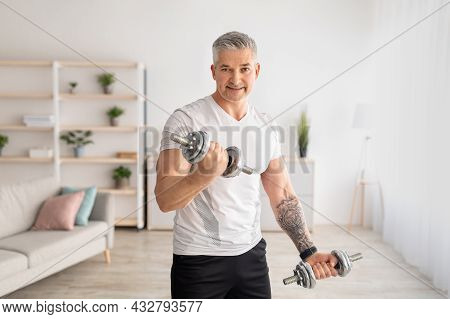 Sporty Mature Man Training With Dumbbells At Home, Working On Arms Strength, Looking And Smiling At