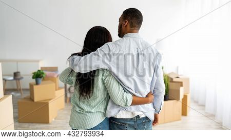 Back View Of Black Husband And Wife Cuddling While Moving To New House, Panorama With Free Space, Pa