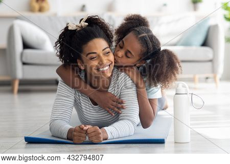 Happy Black Mother And Daughter Cuddling While Practicing Yoga