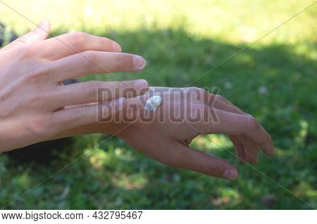 Woman's Hand With Skincare Cream On Nature Background. Female Hands Use Cosmetic Cream. Hydrating An