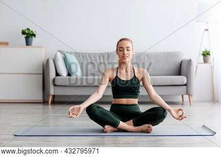 Calm Caucasian Pretty Young Blonde Lady With Closed Eyes Practicing Yoga, Breath, Exercising At Home