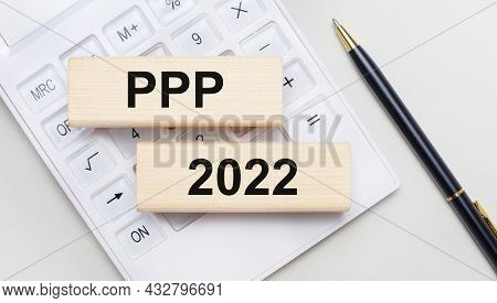 Wooden Blocks With The Text Ppp 2022 Lie On A Light Background On A White Calculator. Nearby Is A Bl
