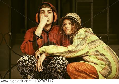 Young fashion hipster couple sitting at the iron fence Stylish trendy man and woman in hoodie sweatshirt