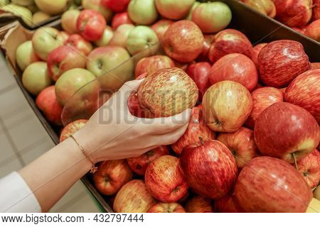 Female Hands Check Red Apples In Supermarket.