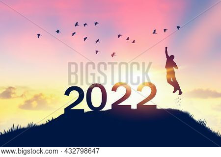 Man Jumping On Sunset Sky With Birds Flying At Top Of Mountain And Number Like 2022 Abstract Backgro