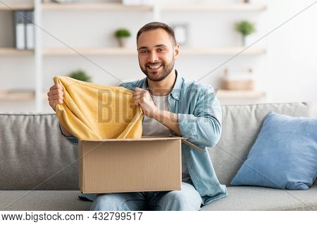Happy Caucasian Guy Unboxing Cardboard Parcel, Satisfied With Successful Shopping, Taking Out New Sw