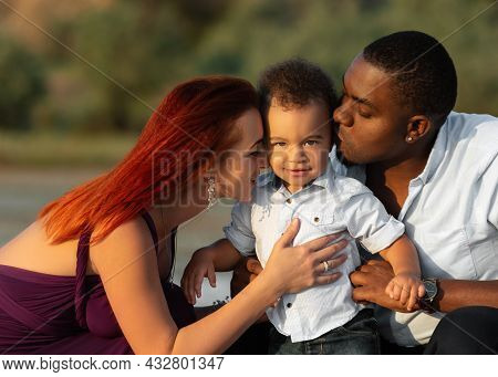 Sweet Adorable Kid Smiles While His Parents Kissing And Hugging Him. Picture Of Lovely Mixed Race Fa
