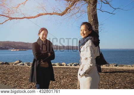 Two Beautiful Girls In Trench Coats Happily Smiling On The Beach Lifestyle Concept