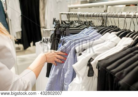 Woman In The Mall Chooses A Blouse.