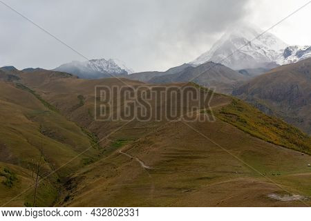 Landscape Views Of The Surrounding Mountains In Autumn Colours And The Snow Covered Peaks In The Bac