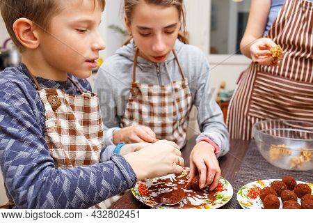 Family Cooking Sweets At Home Kitchen. Boy And Girl With Their Mother Make Healthy Sweets With Fruit