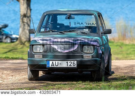 Koknese, Latvia - May 01, 2021: Colorful Oldtimer Pancars Rental Car Fiat 126 Parked On The Side Of