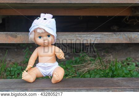 Cute Kewpie Doll In Hat And Shorts Sits On Rustic Wooden Bench In Country House Yard Space For Text.