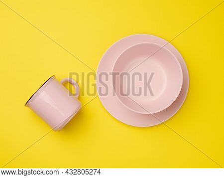 Pink Ceramic Mug And Empty Ceramic Plate On Yellow Background, Top View