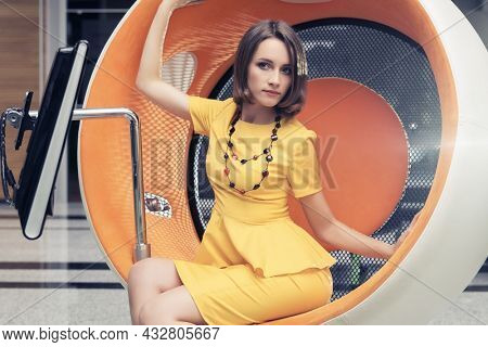 Young fashion business woman sitting on computer chair in office Stylish female model with bob hairstyle in yellow peplum dress
