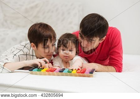 Happy young family with little baby girl playing xylophone toy on blanket at home