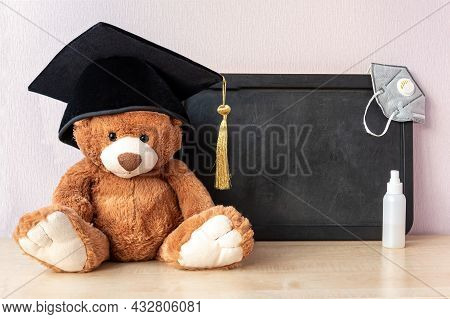 Teddy Bear With Academic Cap Sits Near Blank Blackboard With Medical Mask And Antiseptic On Wooden T