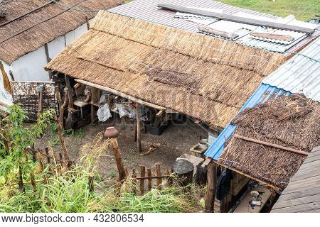 Roof Of Ancient Barn Covered With Dry Reeds Near Traditional Country House On Spring Day View From A
