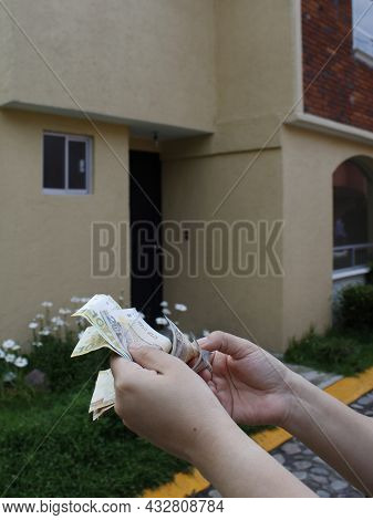 Hand Of A Woman Holding Peruvian Banknotes And Background With Facade Of A House