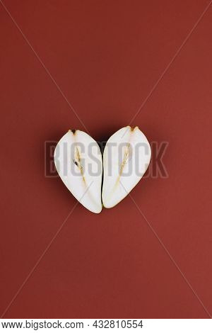 Heart Shaped Pear Fall Composition On Dark Burgundy Background. Top View, Flat Lay. Creative Autumn