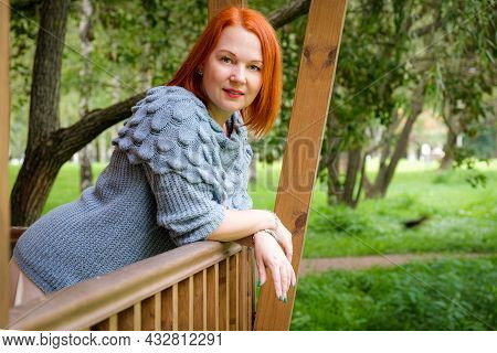 Attractive Young Red-haired Woman In A Skirt And A Knitted Sweater Stands On The Wooden Terrace Of H