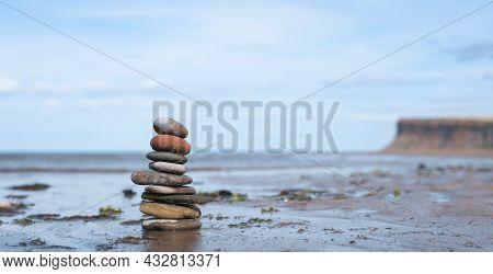 Pebble Tower By Seaside With Blurry Mountain Background, Stack Of Zen Rock Stones On The Sand, Nine