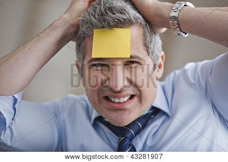 Portrait Of A Businessman With Adhesive Note On Forehead