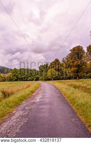 View Of A Long Asphalt Country Road Among Fields And Meadows On A Cloudy Day.