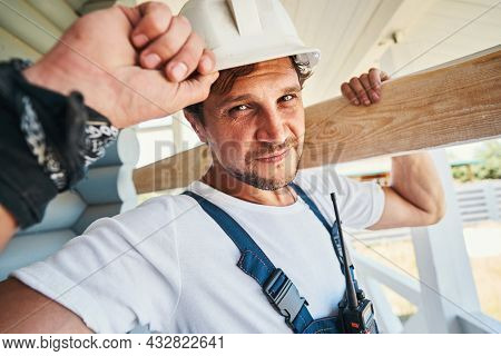 Hard-working Builder Adjusting His Hard Hat While Carrying Board