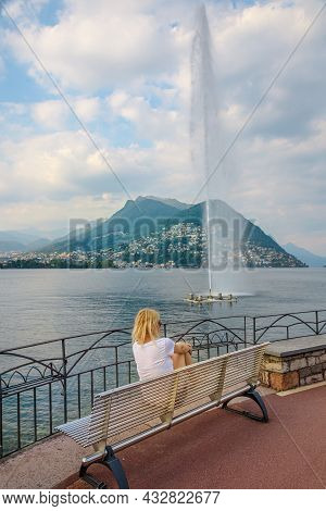 Woman Looking Water Jet Of Paradiso Fountain Of Lugano City In Lugano Lake Of Switzerland. Bench By
