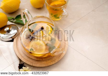 Glass Teapot With Fruit Citrus Tea On Bright Background. Herbal Delicious Healthy Warm Tea, Copy Spa