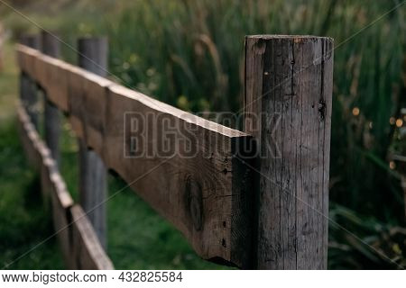 Wooden Rural Fence On A Background Of Green Grass