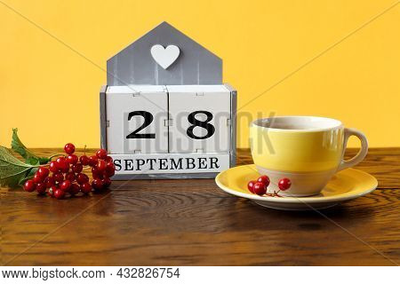 Calendar For September 28 : The Name Of The Month In English, Cubes With The Number 28, A Yellow Cup