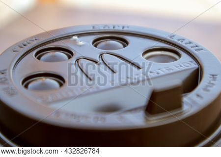Plastic Brown Or Black Disposable Top Coffee Lid With Mcdonald's Fast Food Restaurant Logo Close Up.