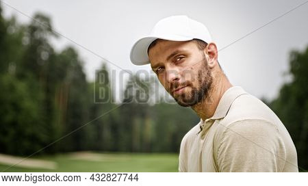 Young man in a cap playing golf on the field close-up