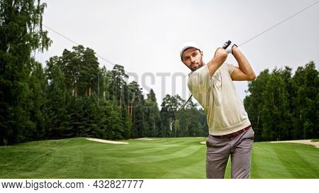 Young man hitting a golf ball with a golf club on the course