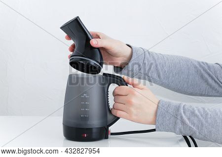 Puts A Replaceable Garment Steamer Head In The Hand Of A Caucasian Woman. White Background.