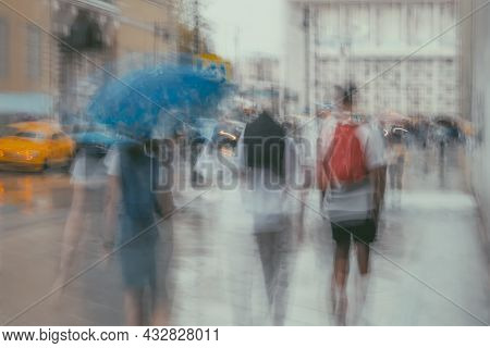 Rainy Evening. Blurred Silhouette Of Abstract Silhouettes Of People Under Umbrellas On Sidewalk Near