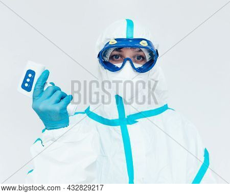 A Medic In A Protective Medical Suit And Mask Holds A Modern Infrared Thermometer In His Hand. Measu